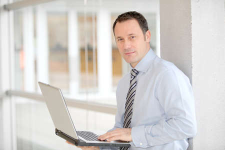 Businessman standing in hall with laptop computer Stock Photo - 8742761