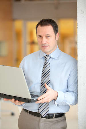 Businessman standing in hall with laptop computer photo