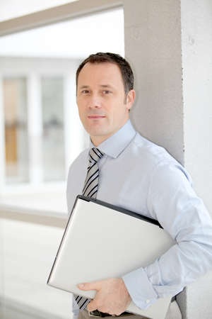 Businessman standing in hall with laptop computer Stock Photo - 8973061