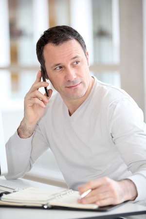 Talking on the phone: Salesman on the phone in the office