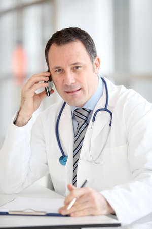 man with phone: Portrait of handsome doctor talking on the phone Stock Photo