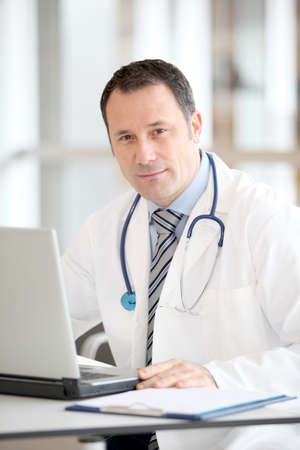 doctor surgeon: Doctor sitting at his desk with laptop computer