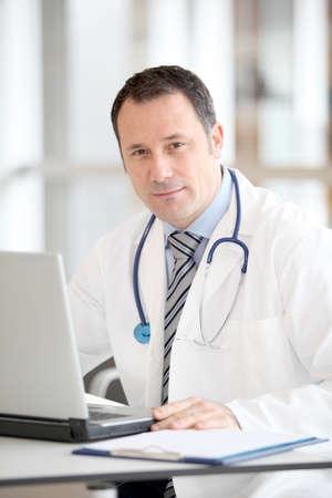 uniformes de oficina: M�dico sentado en su escritorio con ordenador port�til