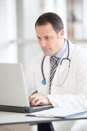 doctor computer: Doctor sitting at his desk with laptop computer