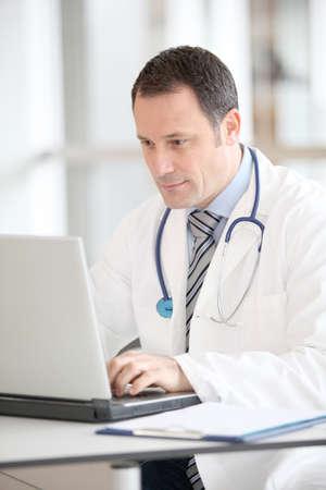 dottore stetoscopio: Medico seduto alla sua scrivania con computer portatile