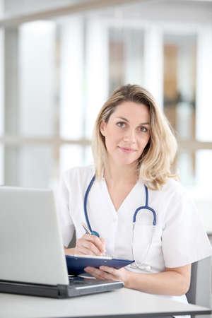 nurse uniform: Hermosa enfermera en el hospital de escritura en el Bloc de notas