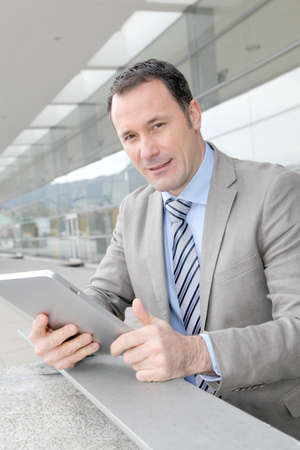 Businessman using electronic tab outside congress center photo