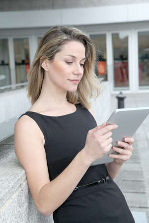 Businesswoman using electronic tab outdoors photo