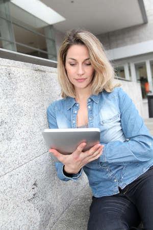 Beautiful woman using electronic tab in the street photo