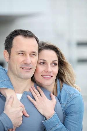 personas abrazadas: Retrato de la feliz pareja permanente al aire libre Foto de archivo