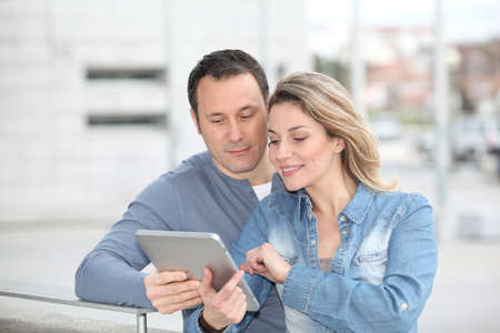 Couple using electronic tab in the street photo