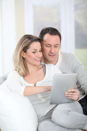 Couple sitting in sofa with electronic tab photo