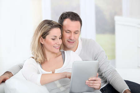 cocooning: Couple sitting in sofa with electronic tab Stock Photo