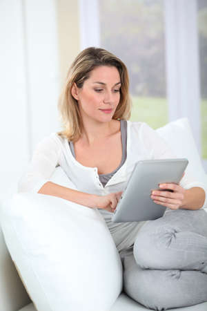 Woman using electronic tab sitting in couch photo
