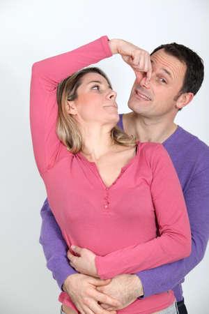 pinch: Woman pinching her boyfriends nose Stock Photo