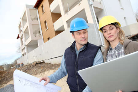 Architect and engineer looking at plan on construction site photo