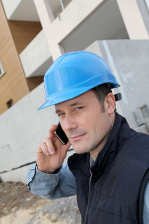 Supervisor talking on the phone on construction site  photo