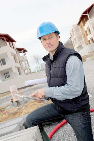 Supervisor using electronic tab on construction site photo