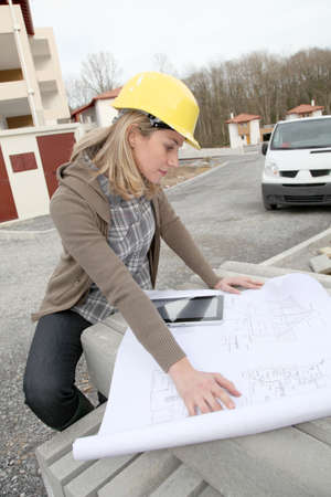 Woman engineer looking at plan on construction site photo