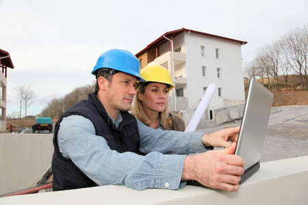 foreman: Architect and engineer looking at plan on construction site Stock Photo