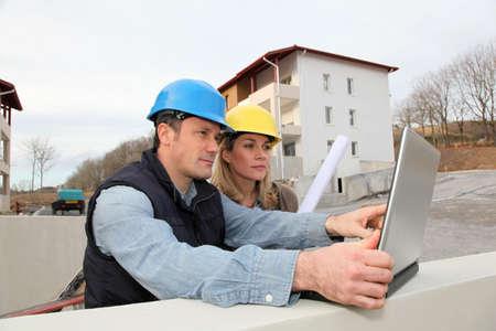 建築家とエンジニアの工事現場でプランを見る