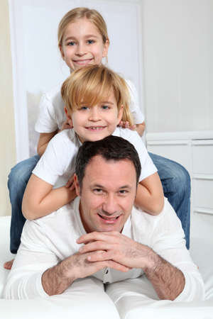 Portrait of father and children laying in sofa photo