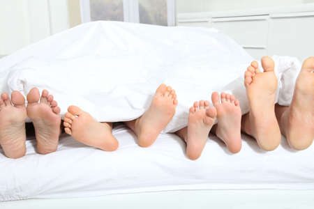 bedding indoors: Closeup of family feet in bed