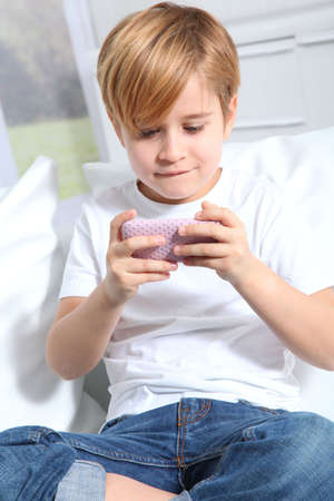 Portrait of little blond kid playing video game photo