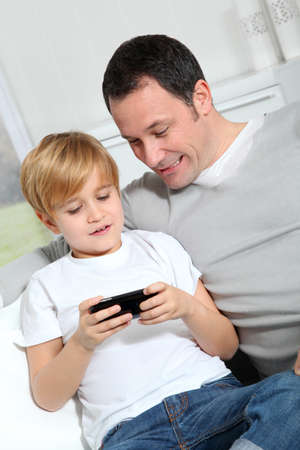 Father and son playing video game at home photo