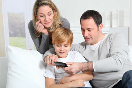 family on couch: Family playing video game on smartphone