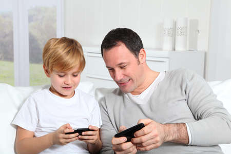 Father and son playing video game at home Imagens