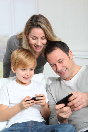 woman smartphone: Family playing video game on smartphone