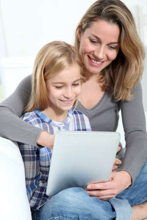 Mother and daughter using electronic tab photo