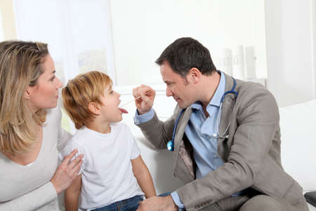 pharyngitis: Doctor examining little boy throat Stock Photo