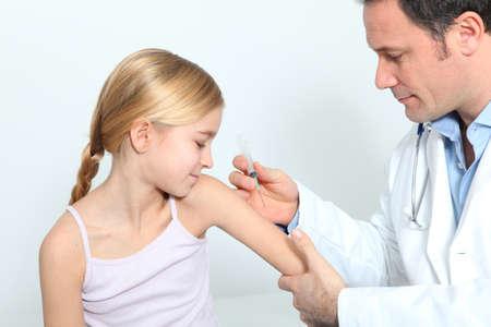 vacunaci�n: Doctor haciendo la inyecci�n de la vacuna a ni�a rubia Foto de archivo