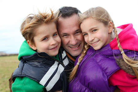 single parent: Portrait of man with 2 children out in the countryside