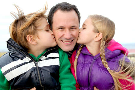 father with children: Kids giving a kiss to their daddy Stock Photo