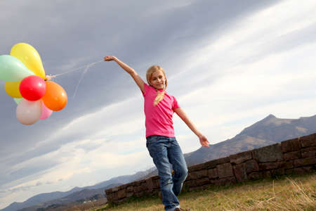 Little girl holding balloons out in the countryside Stock Photo - 8973864