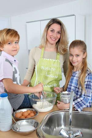 Mother and children in kitchen preparing cake photo