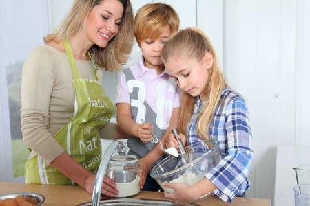 Madre y los ni�os en la cocina preparando pastel Foto de archivo - 9031518