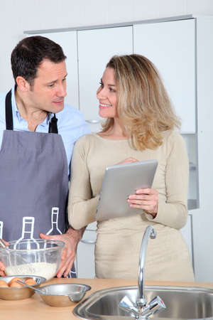 Couple in kitchen looking at recipe on internet photo