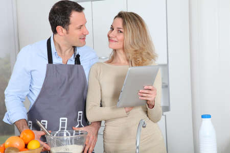 Couple in kitchen looking at recipe on internet Stock Photo - 8974939