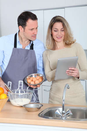 Couple in kitchen looking at recipe on internet Stock Photo - 8974756