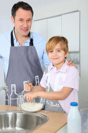Father and son preparing cake in kitchen photo