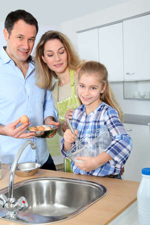 Parents and daughter preparing meal in home kitchen Stock Photo - 9031394