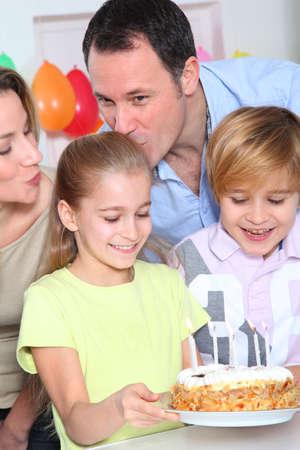 Family celebrating childs birthday photo