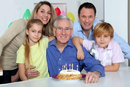 Family celebrating grandfathers birthday photo