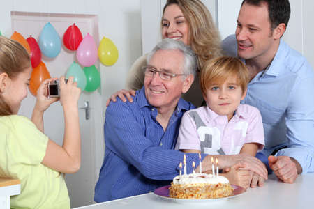 Little girl taking picture of family on birthday celebration photo