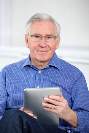 Elderly man connected on internet with electronic tab photo