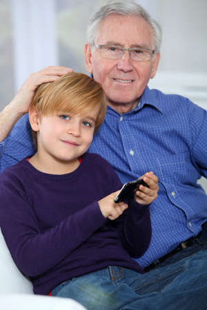 Old man with little boy playing video game on telephone photo